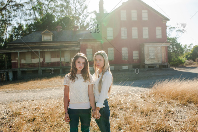 Portrait of a young girl and her mother standing in front of an abandoned building