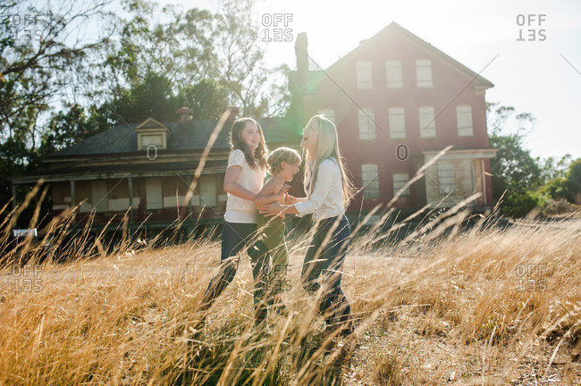 A family of three horsing around in a field near an abandoned building