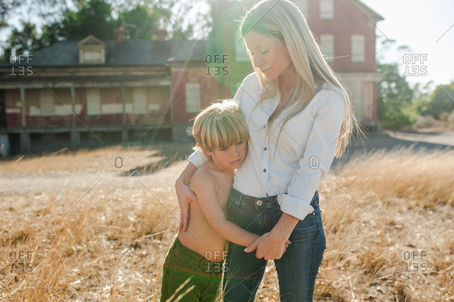 Portrait of a young boy and his mother standing in front of an abandoned building