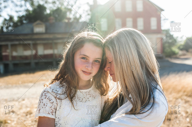 Portrait of a young girl and her mother in front of an abandoned building