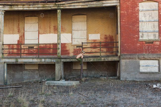 Boy climbing a railing on an abandoned building