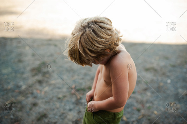 Portrait of a shirtless young boy snapping his pants in the shadow of an abandoned building