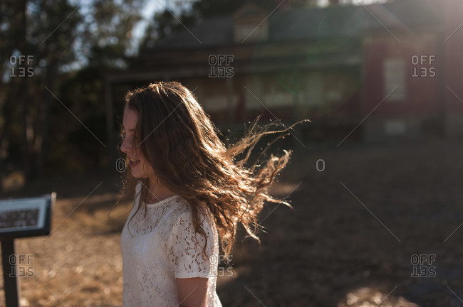 Portrait of a young girl with tousled hair standing in front of an abandoned building