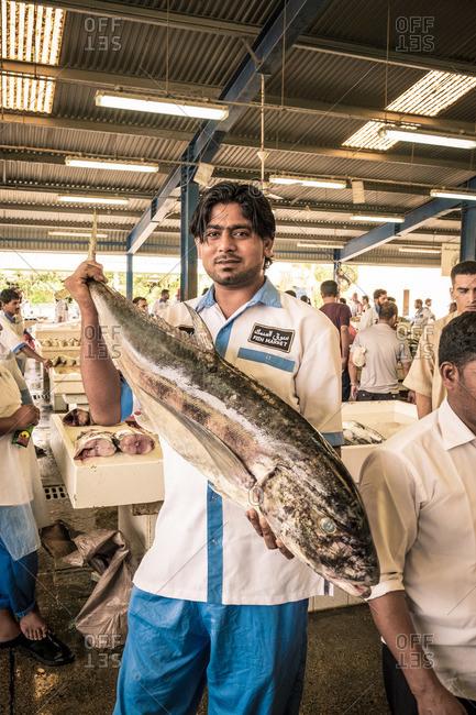Dubai, UAE - May 8, 2015: Market worker holding a large fish at Deira fish market, Dubai
