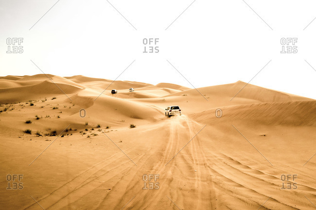 Four wheeled drive vehicles drive over sand dunes in desert, Dubai