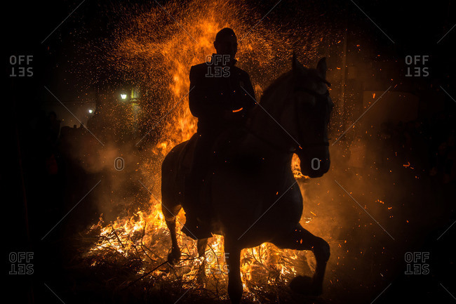 A horseman jumps a bonfire to purify his horse during the Saint Anthony festival, Spain