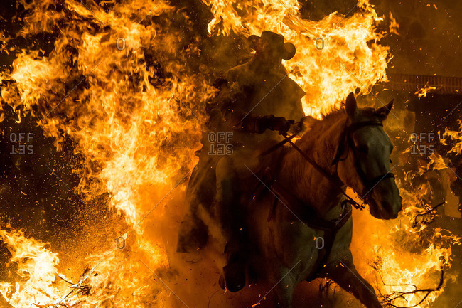 A horseman jumps over a bonfire in Avila, Spain during the religious festival Las Luminarias in honour of Saint Anthony