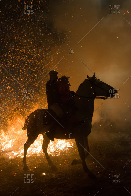 A man and a little girl ride a horse next to a bonfire during 'Las Luminarias' Festival. In honor of Saint Antony, the patron saint of animals, horses are ridden through the bonfires to purify and protect the animal during the year ahead