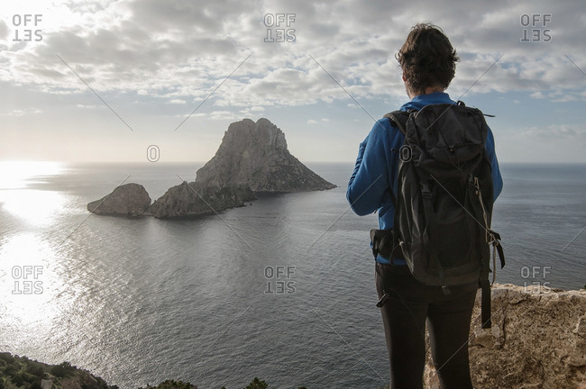 Backpacker overlooking Es Vedra from Ibiza, Spain