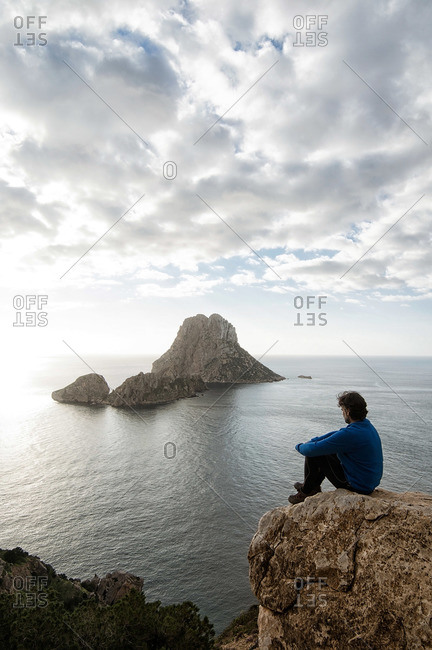Hiker sitting on a rock overlooking Es Vedra from the cliffs of Ibiza, Spain