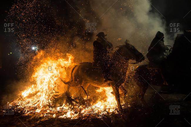 Horsemen jumping a bonfire during the traditional festival of Luminarias, Spain