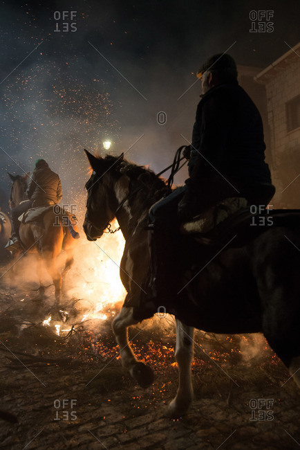 Back view of horseback riders at a bonfire in Avila during the traditional religious festival in honor of Saint Anthony