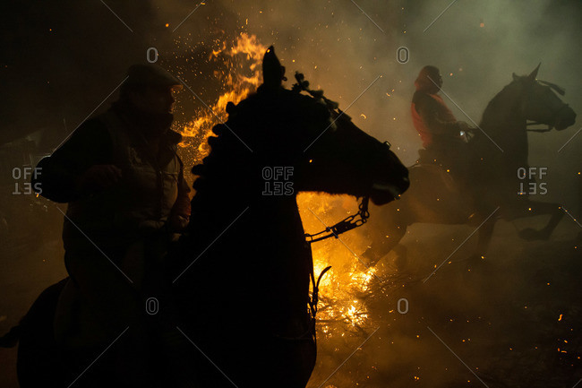 Horse riders silhouetted at Saint Anthony's festival bonfire in Avila, Spain