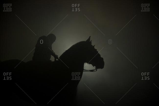 Man on horse silhouetted through the smoke of a bonfire during Las Luminarias Festival, Avila, Spain