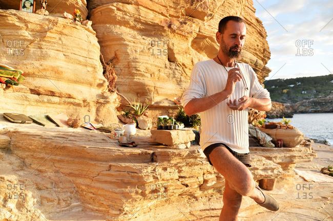 Ibiza, Spain - November 27, 2015: Man doing yoga on rocks at beach in Ibiza, Spain