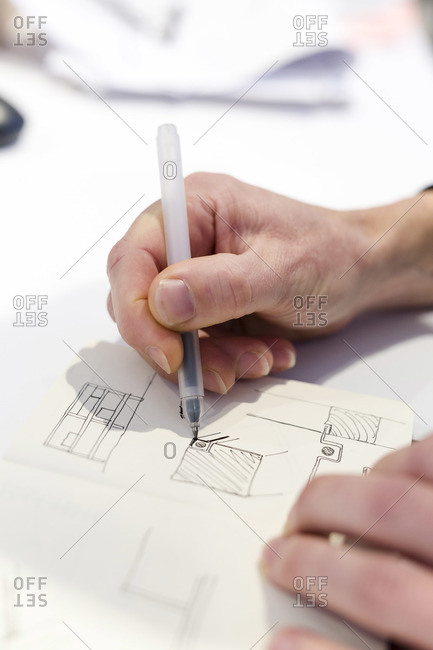 Designer sketching in his notebook inside the factory of a Dutch design furniture brand, Utrecht, The Netherlands