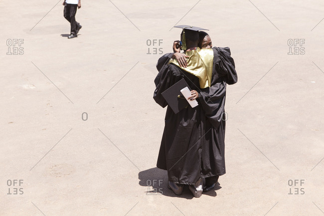 Kigali, Rwanda - February 25, 2011: Two students of a university in Kigali, Rwanda, dressed in graduation gowns and congratulate one another