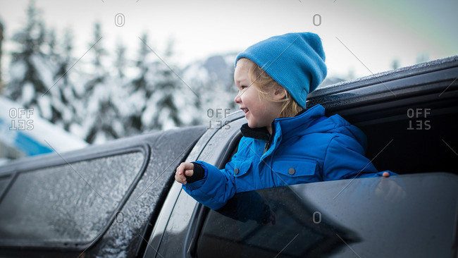 Toddler hanging out a parked truck window in the winter