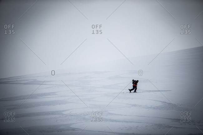 Skier walking up a snowy slope