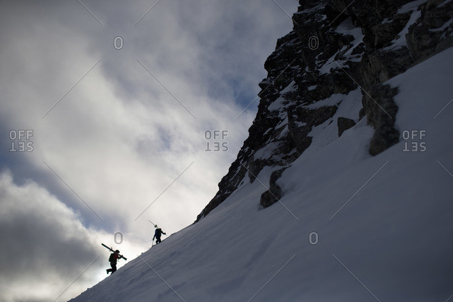 Two skiers walking up a snowy mountain