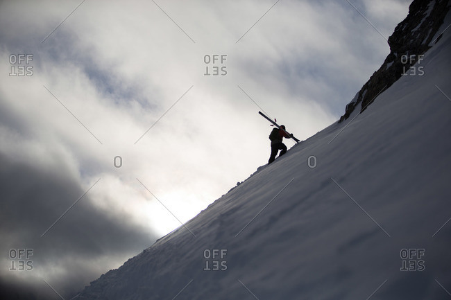 Skier walking up snowy mountain