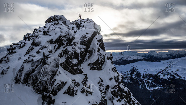 Skier standing atop a snowy mountain