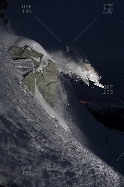 Skier jumping over rock on a slope at night