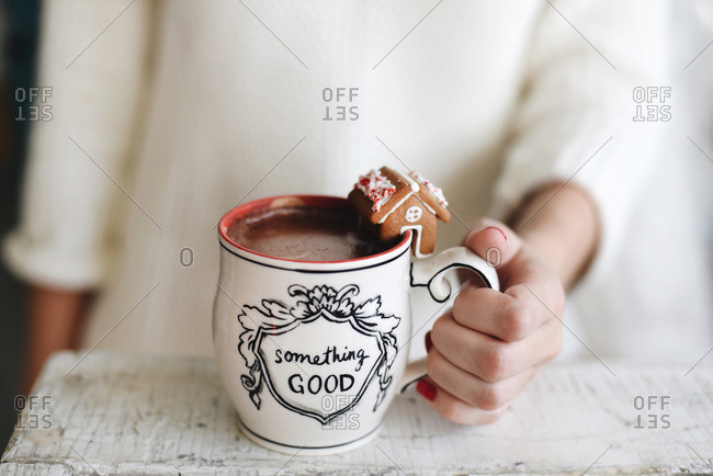 Woman's hand holding a white mug filled with hot cocoa and garnished with a gingerbread house