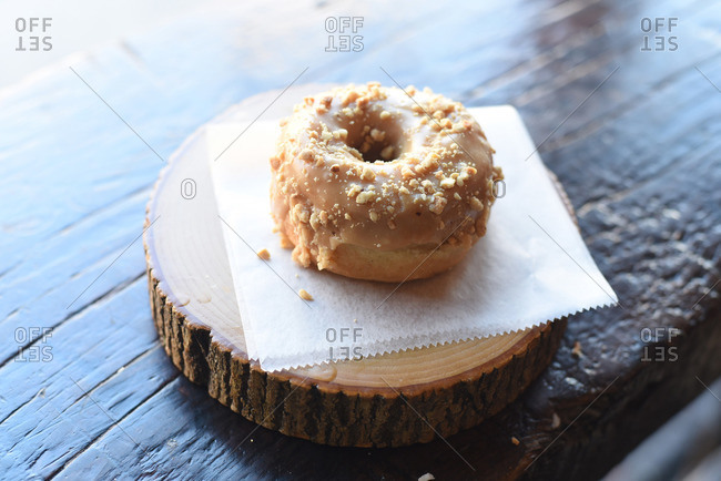 Maple glazed donut encrusted in nuts sitting on a sheet of wax paper on a wood log plate