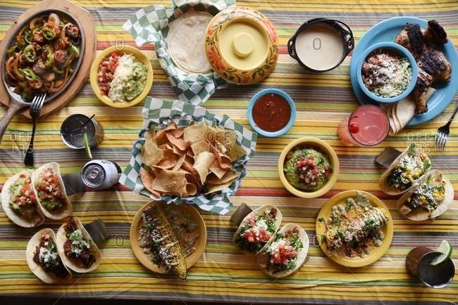 Overhead view of a table spread with Mexican-inspired dishes