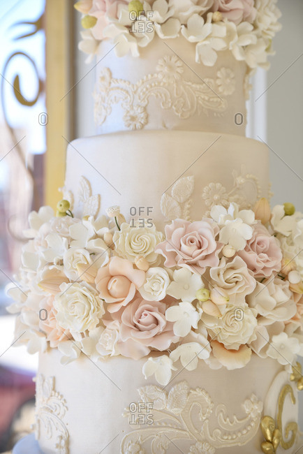 Close-up of a wedding cake with fondant flowers and gold filigree