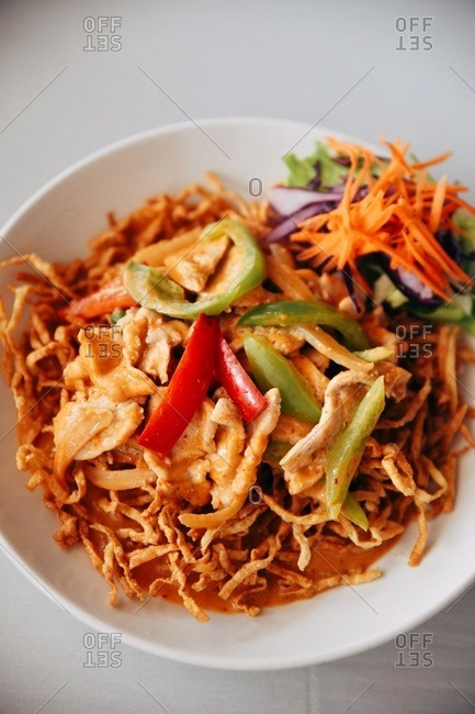 Overhead view of a gourmet Asian dish with crispy noodles and chicken