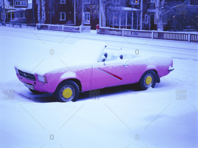 A convertible car covered in snow