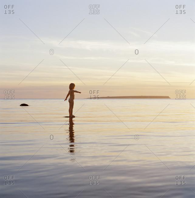 Naked girl standing at sea