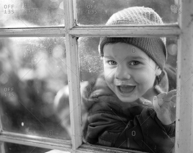 Small boy laughing and looking through window