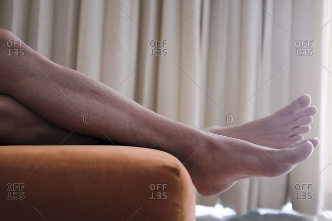 Man relaxing his legs on the edge of an ottoman