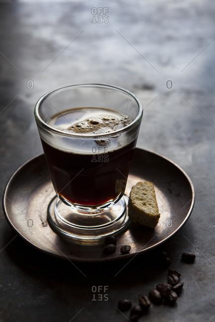 Glass shot of espresso with biscotti