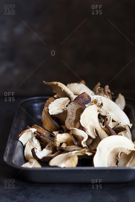 Dried porcini mushrooms piled on a metal dish