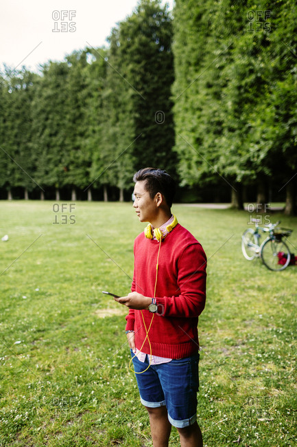 Young man with smartphone in park lined with squared off trees