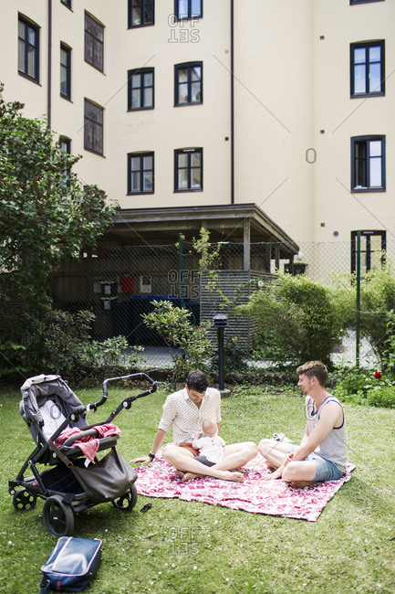 Fathers with their baby in courtyard of apartment building