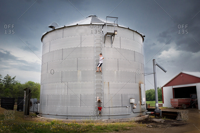 Two boys climbing a grain bin on a farm