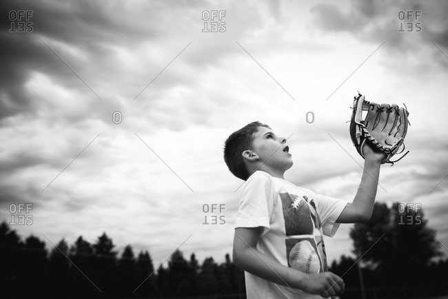 Boy playing baseball who is wearing a mitt and ready to catch