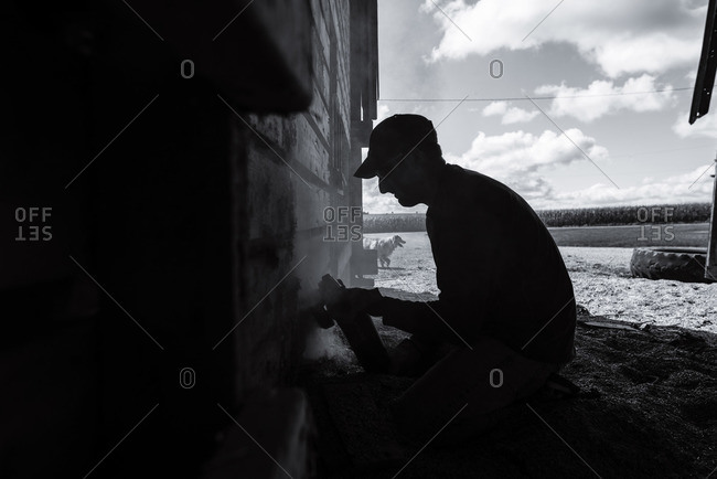 Silhouette of a man working on the side of a barn