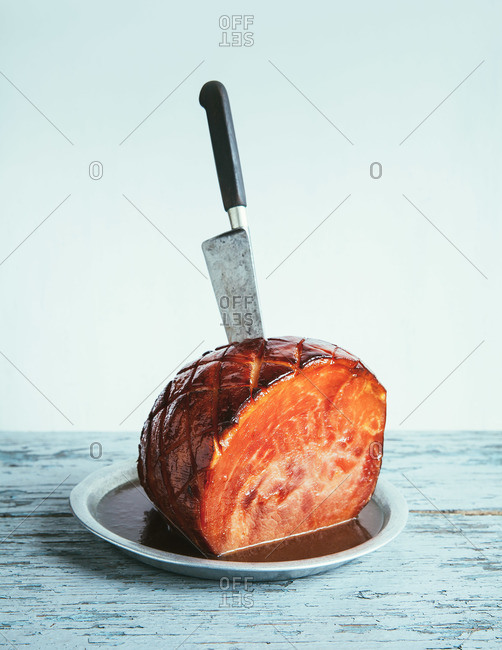 Glazed ham on plate with chef's knife sticking out of it