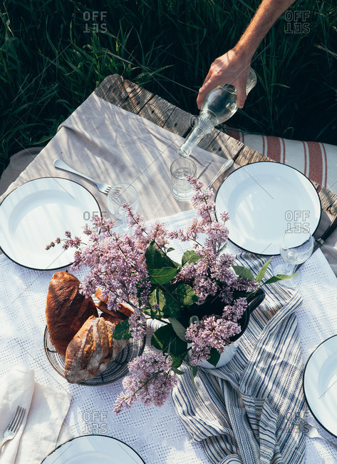 A person pouring water an outdoor table set with bread, plates and lilacs