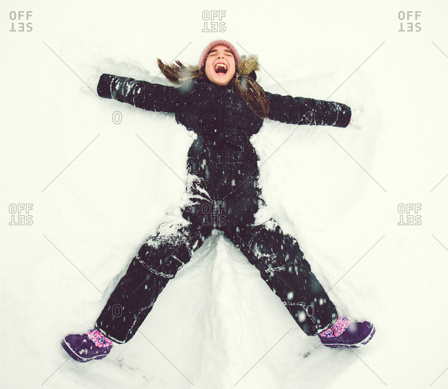 Little girl making a snow angel