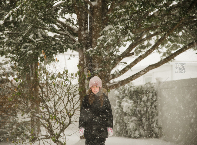 Little girl with standing under a tree in the winter