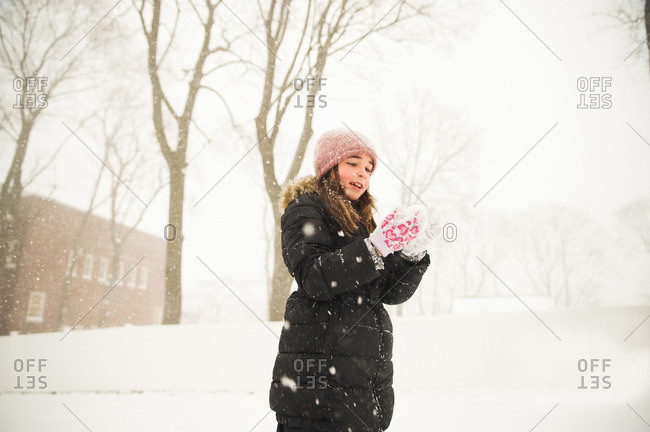 Little girl playing in the snow looking at her hands