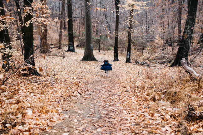Back view of young girl in a blue coat running joyfully down a forest path in autumn