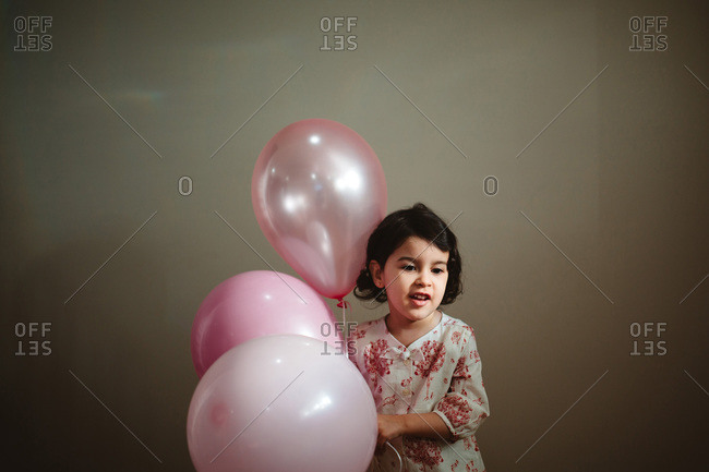 Portrait of a young girl holding pink balloons